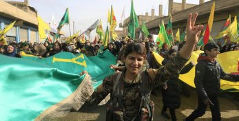 """Members of the Kurdish People's Protection Units (YPG) and Syrian-Kurds take part in a demonstration in the town of Amuda, some 30 kilometres west of Qamishli, a Kurdish-majority city in northeastern Hasakeh province, against a military operation by the Turkish army against the Kurdish YPG forces in Syria's Afrin, on January 21, 2018. Turkey and allied Syrian rebels a day earlier began an air and ground operation, dubbed operation """"Olive Branch"""", aimed at ousting the YPG from Kurdish-majority Afrin. / AFP PHOTO / DELIL SOULEIMAN"""